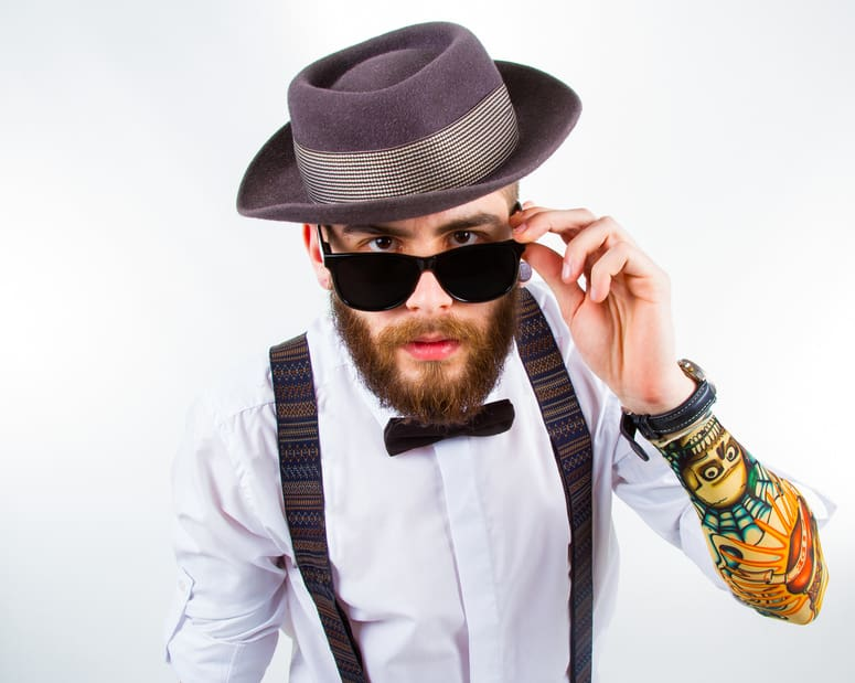 young hipster man wearing hat , suspenders , a bow-tie